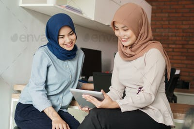 portrait of beautiful muslim women explaining project on tablet to her partner