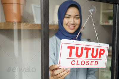 cheerful mature woman in closed sign and smiling while standing against front door