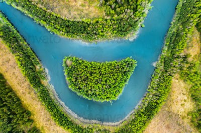 View of the river and the island like a smile from a bird's eye view. Forest zone with a river