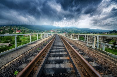 Railroad bridge in mountains in overcast day in summer