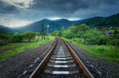 Rural railroad in mountains in overcast day. Old railway