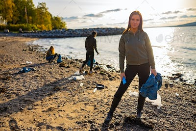 Serious young woman cleaning beach for plastic with volunteers during sunset