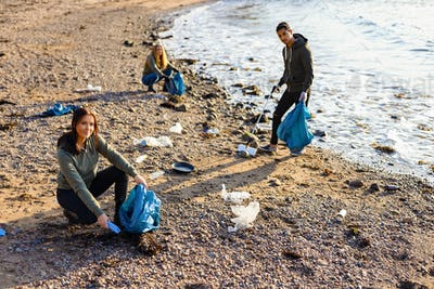 Young woman in a team picking up plastic garbage in bag at beach