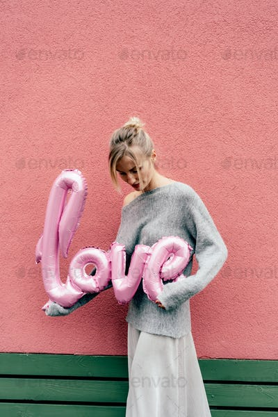 Cute blonde holds a big inflatable word LOVE standing against a pink wall outside.