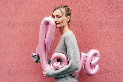 Young charming beauty in a gray sweater hugs the inflatable word LOVE against a pink wall.
