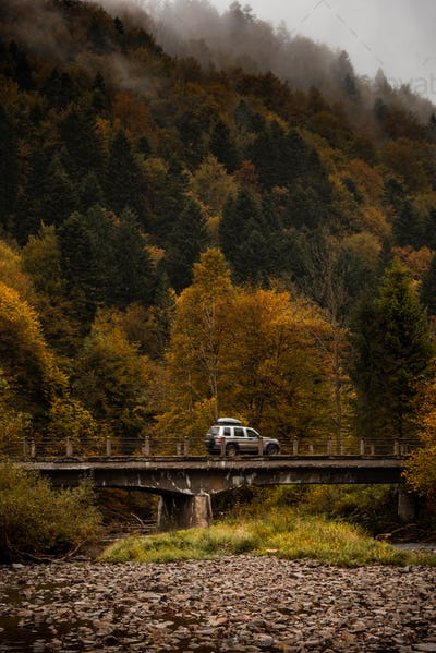 Adventure Road Trip. Car Drives Over Old Bridge in Mountains. Active Outdoor in Wilderness