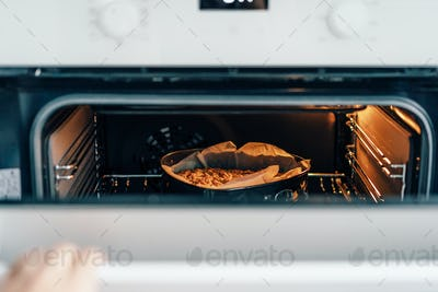There is a pie in the oven. Homemade fragrant baked goods.