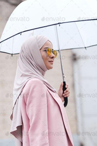 Young stylish Muslim woman in hijab, sunglasses and cardigan holding umbrella