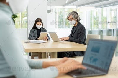 Two busy colleagues in smart casualwear and protective masks networking by table
