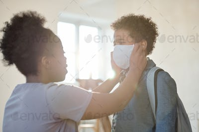 Young careful mother putting protective mask on face of her adorable little son