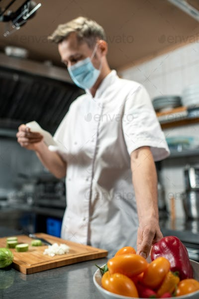 Contemporary young chef in uniform and protective mask taking bowl with capsicum