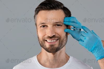 Happy man getting anti-wrinkle injection in eye zone
