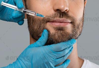 Unrecognizable bearded man getting lips filler in beauty salon