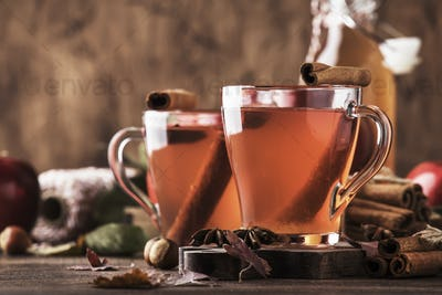 Hot mulled apple cider with with cinnamon sticks, cloves and anise