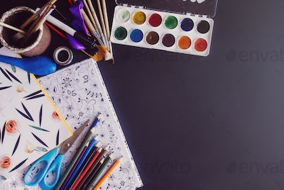 back to school concept, colorful pencils paints brushes scissors and notebook
