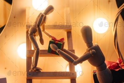 stylish wooden figurines giving present on wooden background with lights, eco gift concept card