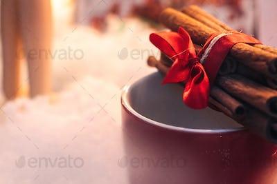stylish aromatic cinnamon sticks on red cup on white background, seasonal greetings