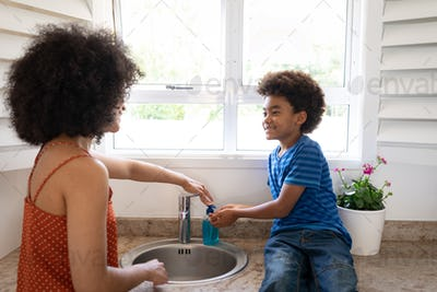 Mother helping son to wash his hands at home