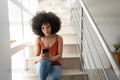 Woman using smartphone while sitting on stairs