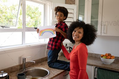 Mother and son holding rainbow painting in the kitchen