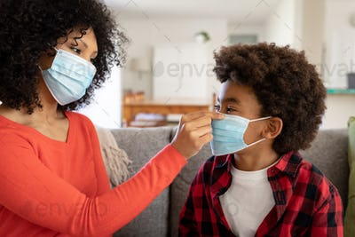 Mother putting face mask on her son at home