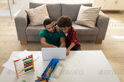 Father and son using laptop at home