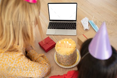 Mother and daughter in party hat using laptop at home