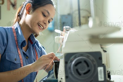 Asian female employees sew using embroidery machines