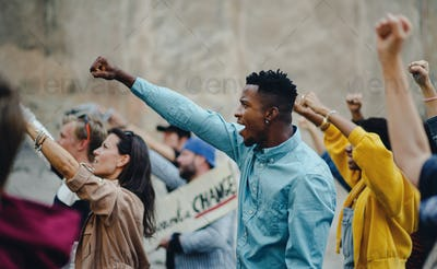Group of people activists with raised fists protesting on streets, BLM demonstration concept.