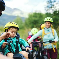 Family with tired small children cycling outdoors in summer nature.