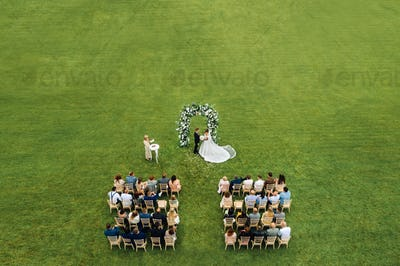 Top view of the Wedding ceremony in a green field with guests sitting on chairs. Wedding venue on