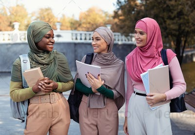 Three Muslim Female Students In Hijab Holding Books Standing Outdoors