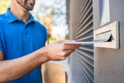 Postman putting letter in mailbox.