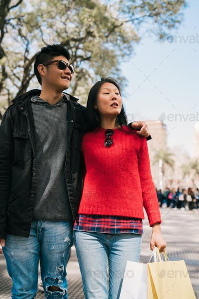 Asian couple walking in the city.