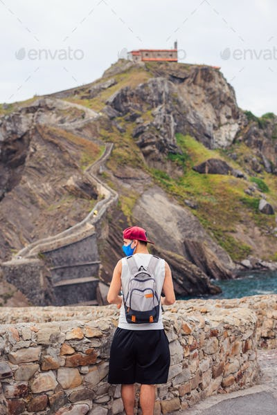 Young tourist with a surgical mask in front of the gaztelugatxe Island