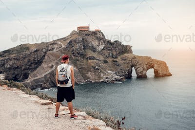 Young man with a hat in front of the Gaztelugatxe Island