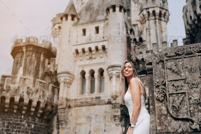 Young woman in front of a medieval castle