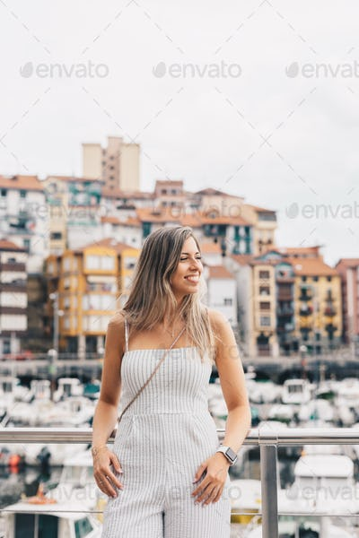 Young woman in front of a small village port