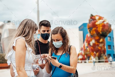 Group of friends with surgical masks searching on a smartphone