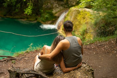 Couple on a blue pond with a waterfall