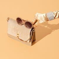 Fashion and gold. Female hand, Stylish jewelry, handbag clutch.