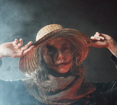 Woman in fashion of scarecrow hold on to her hat