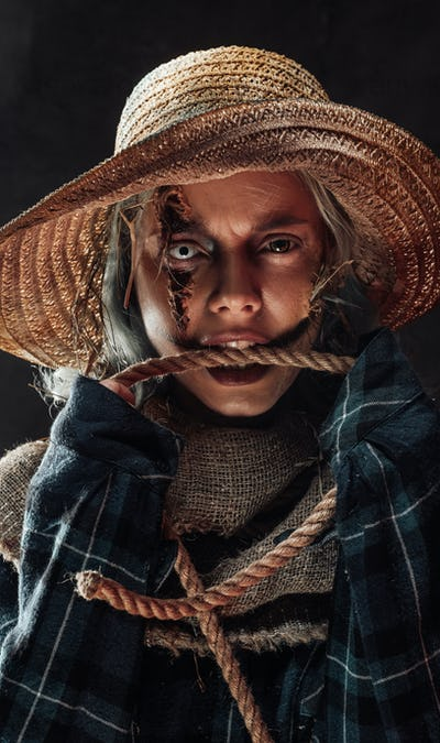 Woman dressed like scarecrow biting a rope in dark background
