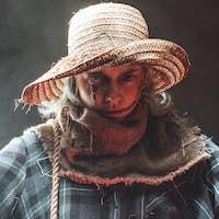 Woman dressed like scarecrow posing in dark background