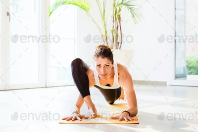 Front view of a woman doing a lizard yoga pose