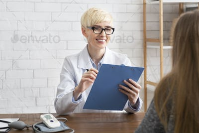 Friendly smiling adult female doctor in glasses, white coat makes notes on tablet and looks at lady