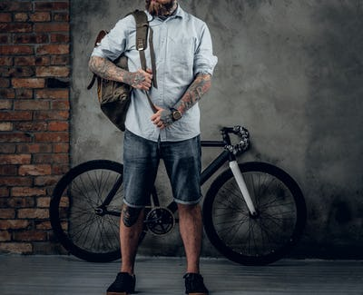 Portrait of bearded hipster male with bag and bicycle.