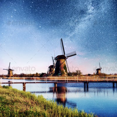 Colorful spring night with traditional Dutch windmills canal in Rotterdam. Wooden pier near the lake