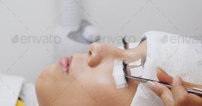Woman having eyelash extension in beauty salon