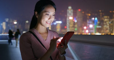 Woman check on mobile phone at night
